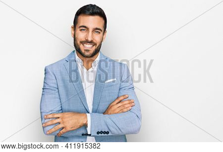 Young hispanic man wearing business jacket happy face smiling with crossed arms looking at the camera. positive person.
