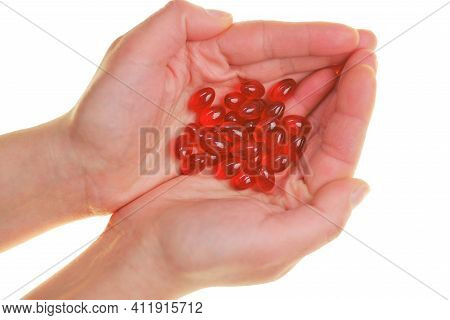 Krill Oil Capsules. Red Gelatin Capsules With Krill Oil In Hand On White Background.source Of Omega