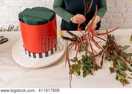 Florist Workplace On The Background Of A White Brick Wall. An Experienced Florist Prepares The Base