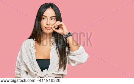Young beautiful hispanic girl wearing casual clothes mouth and lips shut as zip with fingers. secret and silent, taboo talking