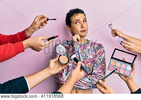 Handsome man wearing make up with make up cosmetics around thinking concentrated about doubt with finger on chin and looking up wondering