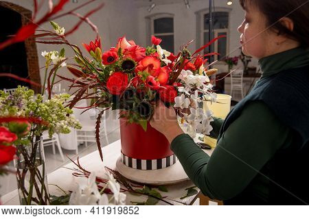 Florist Workplace On The Background Of A White Brick Wall. The Florist Composes A Bouquet Of Orchids