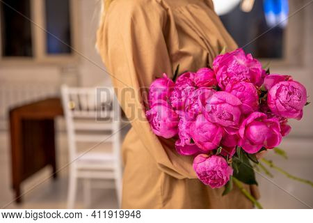 A Mono-bouquet Of Peonies In The Hands Of A Young Florist Girl In A Bright Loft-style Room. Professi