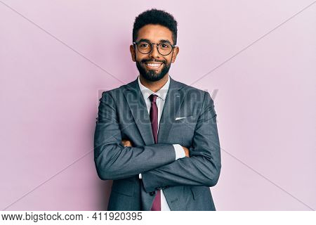 Handsome hispanic business man with beard wearing business suit and tie happy face smiling with crossed arms looking at the camera. positive person.