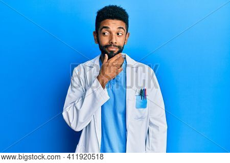 Handsome hispanic man with beard wearing doctor uniform with hand on chin thinking about question, pensive expression. smiling with thoughtful face. doubt concept.