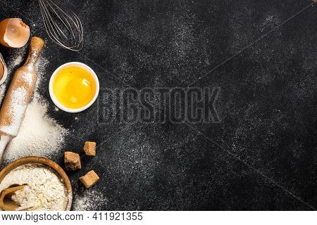 Ingredients For Cooking Baking, Baking Background. Flour, Sugar, Eggs, And Utensil On Black Backgrou