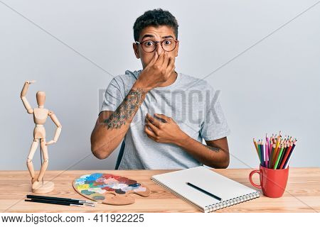 Young handsome african american man painter sitting palette and art manikin smelling something stinky and disgusting, intolerable smell, holding breath with fingers on nose. bad smell