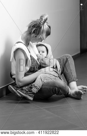 Mom Breastfeeds The Baby, Baby Sucks Breast Milk In Mom's Arms, Lifestyle, Black And White Photo