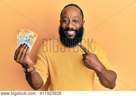 Young african american man holding 10 swiss franc banknotes smiling happy pointing with hand and finger