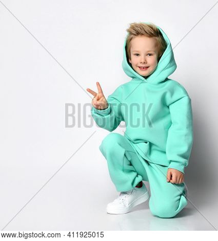 Blond Boy In A Sports Suit And A Hood On His Head Sits On A Gray Background. Child In A Warm Turquoi