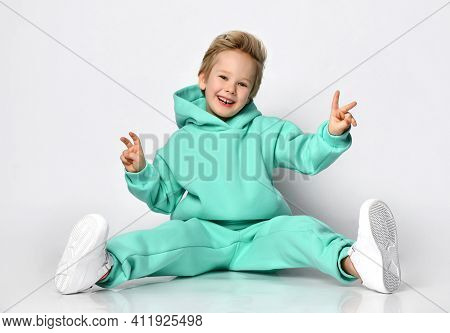 Playful Boy In A Warm Sports Suit And Sneakers Sits On A Background Of A Gray Wall. Child In A Turqu