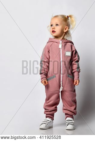 Little Preschooler Girl In Warm Pink Sportswear On A Gray Background. Child Looks To The Side, His H