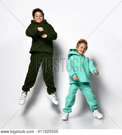 Two Boys In Warm Suits In A Sporty Style Jump On A Gray Background. Children In Green And Turquoise