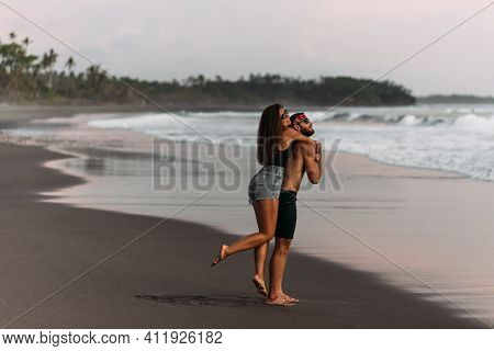 A Man And A Woman Have Fun At Sunset By The Sea. Happy Couple On The Beach. Tanned Couple Having Fun