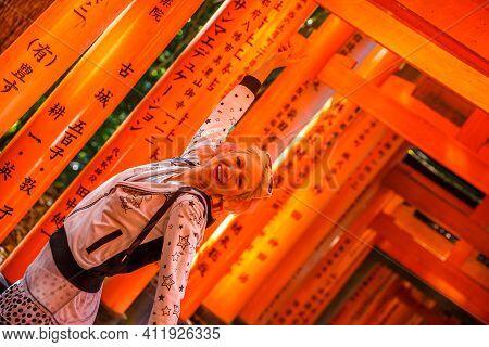 Torii Tunnel Path. Back Of Woman Walking Under Red Torii Gates Of Famous Landmark Fushimi Inari Shri
