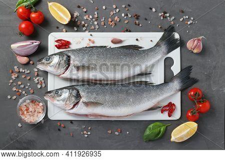 Raw Seabass With Ingredients And Seasonings Like Basil, Lemon, Sea Salt, Pepper, Cherry Tomatoes And