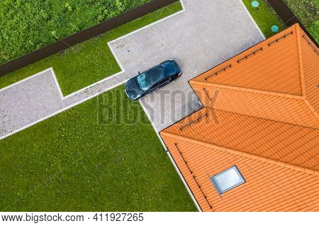 Aerial Top View Of House Shingle Roof With Attic Windows And Black Car On Paved Yard With Green Gras
