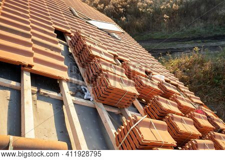 Stacks Of Yellow Ceramic Roofing Tiles For Covering Residential Building Roof Under Construction.