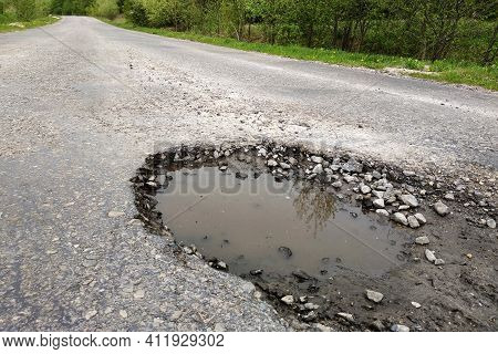 Close Up Of Big Pothole With Dirty Rain Water Of The Road.