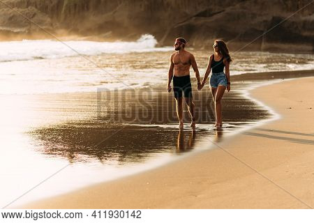 A Happy Couple Walks Along A Sandy Beach On The Island Of Bali. Couple In Love At Sunset By The Sea.