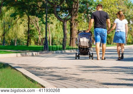 people walking and children playing in a city park on a summer day, green lawns with grass and trees, paths and benches, bright sunlight and shadows
