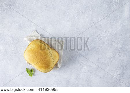 Top View Of Loaf Of Freshly Baked Bread With Parsley On Linen Towel Over Light Gray Concrete Backgro
