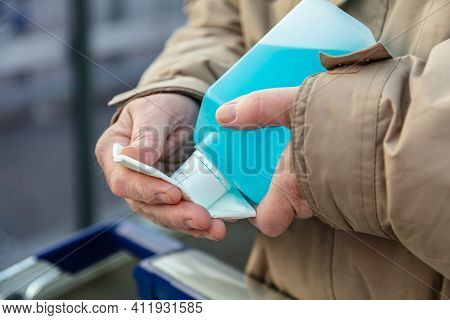 Mans Hand Hold A Plastic Bottle With Disinfectants, For Using The Handle Of A Shopping Cart Get Disi
