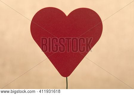 Decorative Felt Heart On Wire Over Beige Background