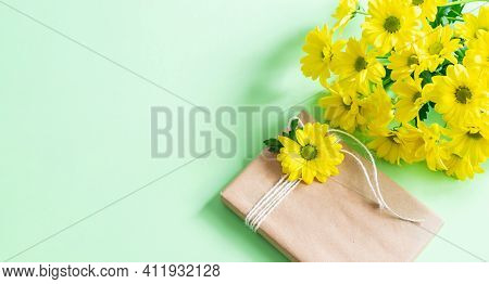 Yellow Chrysanthemums Bouquet And Handmade Gift Box Wrapped Craft Paper On The Table. Mock Up Banner