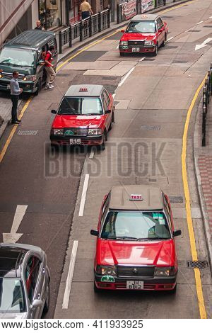 Hong Kong Island, China - May 14, 2010: 3 Red Taxi Cars Driving On Semi-empty Concrete Surface Stree