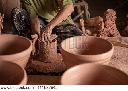 Hand Of Men Working On The Potter's Wheel. Hands Sculpts A Mortar From Clay Pot. Clay Ware Handmade