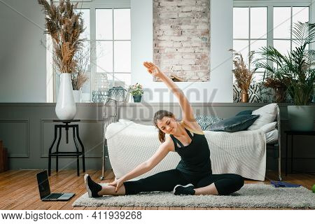 Positive Athletic Woman With Neatly Tied Hair And Tight Sportswear Stretching   At Home. The Young W