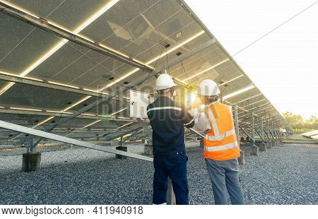 Technician With Engineer Are Check The Performance Of The Solar Panels In The Solar Plant, Alternati