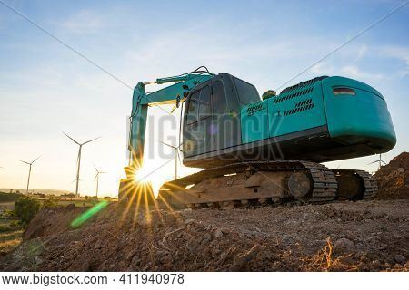 Backhoe And Wind Turbines That Are Generating Electricity In The Background, The Concept Of Sustaina