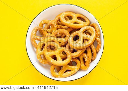 Pretzel In A Plate On An Isolated Background. Pretzel Texture. Salty Curl On The Table.