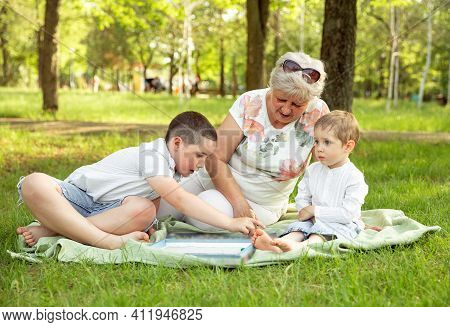 Grandma And Grandchildren. Two Generations Of Family. Young Boys And Grandmother Sitting In Sunny Su