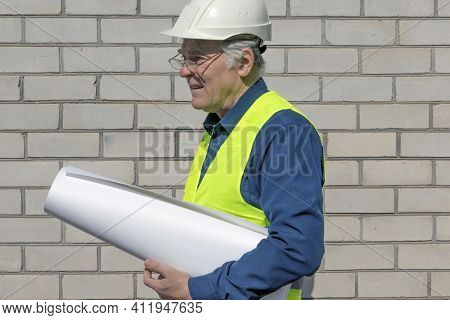 An Attentive Architect In A White Helmet Examines A Project. On A Bright Sunny Day. Architect With D