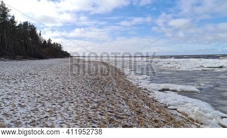 Baltic Sea On Wintertime With Broken Ice Cracks. Large Pieces Of Floating Ice Driven Into The Seasid