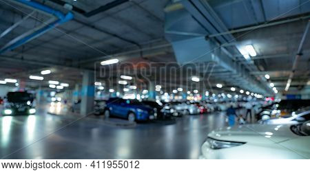 Blur Underground Car Parking Lot Of Shopping Mall With Opened Light. Blur Car Driving And People Wal