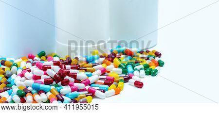 Pile Of Colorful Antibiotic Capsule Pills On Blurred Plastic Drug Bottles. Antibiotic Drug Resistanc