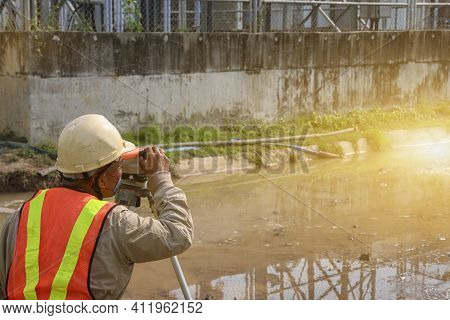 Civil Engineer At Construction Site And A Land Surveyor Using An Altometer