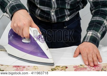 A Man Ironing Clothes On An Ironing Board.