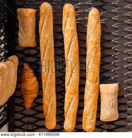 A Baguette, Croissant And Ciabatta. Fresh Baked Wheat Bread Lies On A Metal Grate. Various Kinds Of