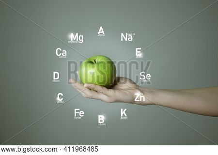 Woman`s Hand Holding Green Apple, Microelement Icons In Clockface Cirlce Shape On Grey Background. W