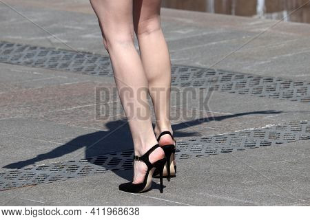 Slim Female Legs On High Heels, Woman In Black Stiletto Shoes Walking On A Street. Concept Of Ladies