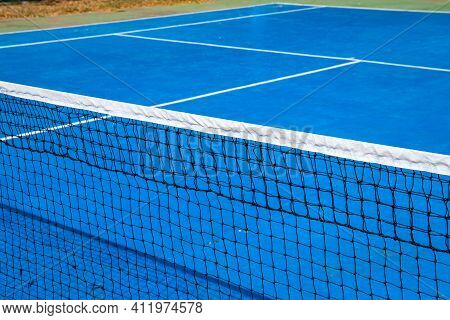 Blue Tennis Court With Net, Sport Field Photo. Lawn Tennis On Hard Court. Sunny Tennis Court Empty A
