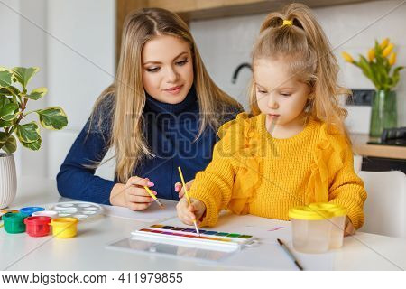 Mother And Daughter Painting At Home. Cute Little Kid In Yellow Sweater Having Fun With Parent And P