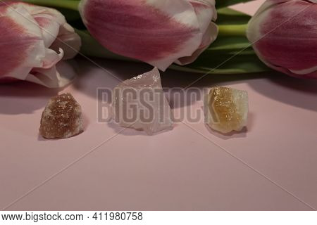 On A Pink Background, There Are Three Pink Tulips And Semi-precious Stones Halite, Rose Quartz, Citr