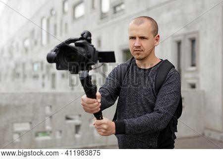 Professional Videographer Shooting Video Using Modern Dslr Camera On 3-axis Gimbal Over Grey Concret