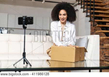 Satisfied Multiethnic Girl Blogger Videotaping Herself, Speaking, Doing An Unpacking Of Clothes, Hel